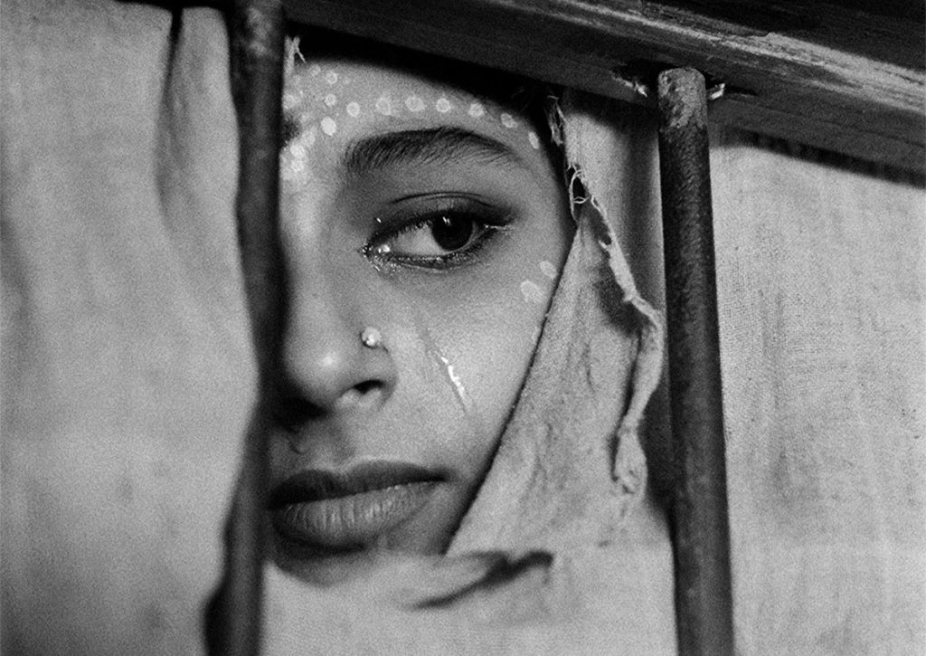 Aparna on the day of the wedding looking through a torn curtain